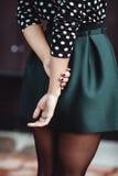 La muchacha que el adolescente en una falda corta se coloca con sus manos Imagen de archivo