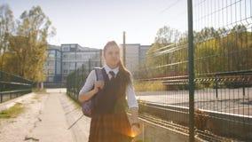 La muchacha que el adolescente volvi? de escuela en la puesta del sol Vuelta de la escuela despu?s de la escuela en la puesta del metrajes