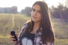 La muchacha que escucha la música y muestra a su jugador mp3 Fotografía de archivo libre de regalías