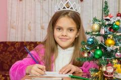 La muchacha que espera un Año Nuevo, escribe una letra a los deseos y mirada en el marco Foto de archivo libre de regalías