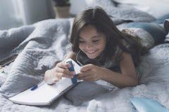 La muchacha, que está sonriendo, miente en una cama gris y escucha la música en los auriculares blancos, sujetando con grapa la h Fotos de archivo libres de regalías