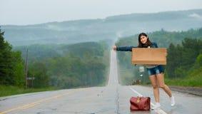 La muchacha que hace autostop soporta una muestra Foto de archivo