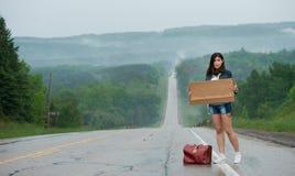 La muchacha que hace autostop soporta una muestra Imagenes de archivo