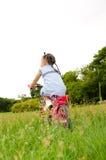 La muchacha que hace girar en la bicicleta. Imagen de archivo