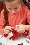 La muchacha que hace punto una bufanda, accesorios de costura, lugar de trabajo de la costurera, muchos se opone para la costura, Imagenes de archivo