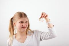 La muchacha que hace un doesn't de la mueca quiere llevar el audífono Foto de archivo