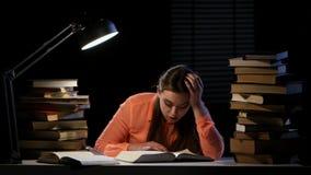 La muchacha que hojea a través de un libro bosteza y se cae dormido Fondo negro almacen de video