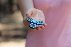 la muchacha que juega al hilandero azul del metal en manos en la calle, las manos femeninas que detienen al hilandero popular de  Foto de archivo