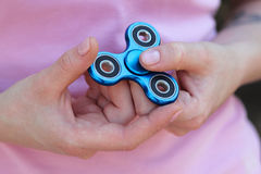 la muchacha que juega al hilandero azul del metal en manos en la calle, las manos femeninas que detienen al hilandero popular de  Imagen de archivo