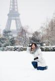 La muchacha que juega bolas de nieve acerca a la torre Eiffel en París Foto de archivo libre de regalías