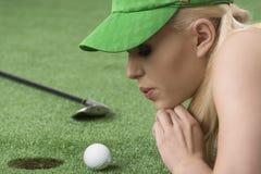 La muchacha que juega con la pelota de golf, ella sopla en ésa Imagen de archivo libre de regalías