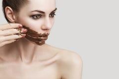 La muchacha que lame el chocolate manchado Foto de archivo