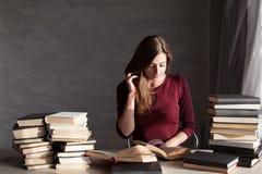 La muchacha que lee un libro en la biblioteca se está preparando para el examen Imagen de archivo