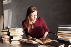 La muchacha que lee un libro en la biblioteca se está preparando para el examen Imágenes de archivo libres de regalías