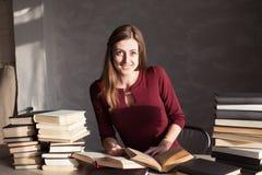 La muchacha que lee un libro en la biblioteca se está preparando para el examen Imagenes de archivo