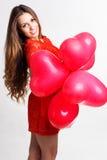 La muchacha que lleva a cabo el corazón rojo hincha, día de tarjetas del día de San Valentín Fotos de archivo