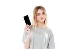 La muchacha que lleva a cabo el espacio en blanco scren el teléfono móvil y la mirada de la cámara Imagen de archivo libre de regalías