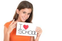 La muchacha que lleva a cabo una muestra con las palabras I ama la escuela Imágenes de archivo libres de regalías
