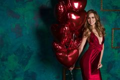 La muchacha que lleva el corazón rojo de los globos del vestido y del rojo forma para Valentin Foto de archivo