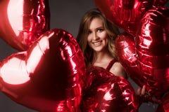 La muchacha que lleva el corazón rojo de los globos del vestido y del rojo forma para Valentin Fotos de archivo libres de regalías
