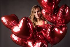 La muchacha que lleva el corazón rojo de los globos del vestido y del rojo forma para Valentin Fotografía de archivo