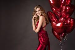 La muchacha que lleva el corazón rojo de los globos del vestido y del rojo forma para Valentin Imagenes de archivo