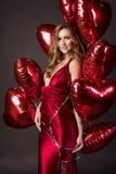 La muchacha que lleva el corazón rojo de los globos del vestido y del rojo forma para Valentin Fotografía de archivo libre de regalías