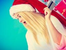 La muchacha que lleva el sombrero de Papá Noel sostiene la tarjeta de crédito para comprar Imagenes de archivo