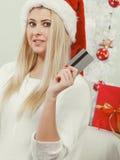 La muchacha que lleva el sombrero de Papá Noel sostiene la tarjeta de crédito para comprar Foto de archivo libre de regalías