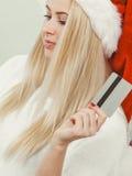 La muchacha que lleva el sombrero de Papá Noel sostiene la tarjeta de crédito para comprar Foto de archivo