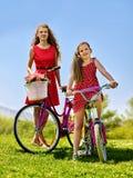 La muchacha que lleva el vestido rojo monta la bicicleta en parque del verano Fotografía de archivo libre de regalías