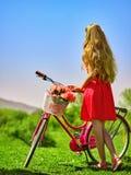 La muchacha que lleva lunares rojos viste paseos monta en bicicleta en parque Imagenes de archivo