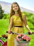 La muchacha que lleva lunares rojos viste paseos monta en bicicleta en parque Foto de archivo