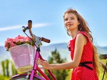 La muchacha que lleva lunares rojos viste paseos monta en bicicleta en parque Imagen de archivo libre de regalías