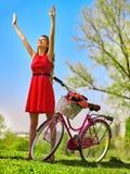 La muchacha que lleva lunares rojos viste paseos monta en bicicleta en parque Fotografía de archivo