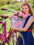La muchacha que lleva sundress azules de los lunares monta la bicicleta con la cesta de las flores Foto de archivo libre de regalías