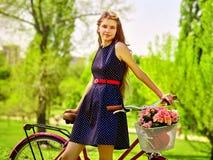 La muchacha que lleva sundress azules de los lunares monta la bicicleta con la cesta de las flores Imágenes de archivo libres de regalías