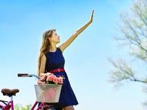 La muchacha que lleva sundress azules de los lunares monta la bicicleta con la cesta de las flores Imagen de archivo libre de regalías