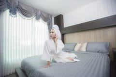 La muchacha que lleva una albornoz en el dormitorio Imagenes de archivo