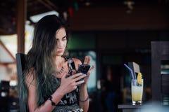 La muchacha que mecanografía en el teléfono, sentándose en un café con el jugo de piña de la fruta en un vidrio y un tubo Fotos de archivo libres de regalías
