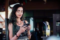 La muchacha que mecanografía en el teléfono, sentándose en un café con el jugo de piña de la fruta en un vidrio y un tubo Fotografía de archivo libre de regalías