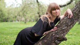 La muchacha que miente en un árbol Foto de archivo libre de regalías