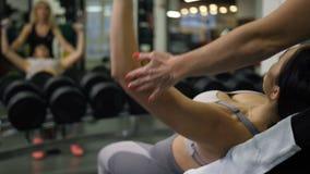 La muchacha que miente en un banco que hace un ejercicio con pesas de gimnasia, un instructor de la mujer ayuda a su 4K MES lento metrajes