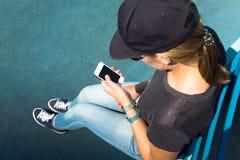 La muchacha que mira el teléfono Imagenes de archivo