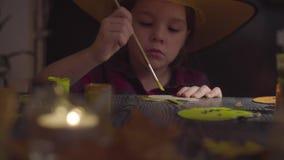La muchacha que pinta la araña Preparación para la celebración de Halloween almacen de video
