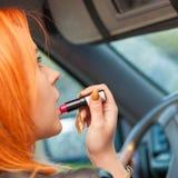 La muchacha que pinta su hacer de los labios compone mientras que conduce el coche Fotografía de archivo libre de regalías