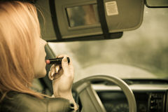 La muchacha que pinta su hacer de los labios compone mientras que conduce el coche Imagenes de archivo
