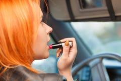 La muchacha que pinta su hacer de los labios compone mientras que conduce el coche Imagen de archivo