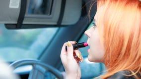 La muchacha que pinta su hacer de los labios compone mientras que conduce el coche Foto de archivo libre de regalías