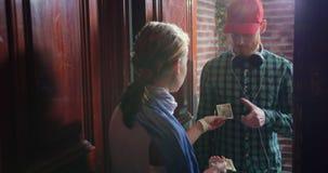 La muchacha que recibe el regalo de la entrega del mensajero encajona y pone la firma en recibo almacen de video